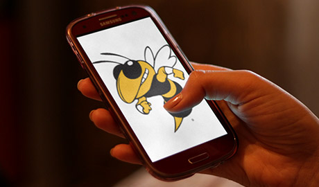 A hand holding a cell phone with image of Buzz the yellow jacket on it.