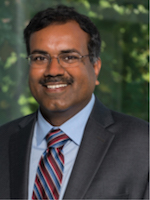 headshot of Srinivas in a grey suit with a blue collared shirt