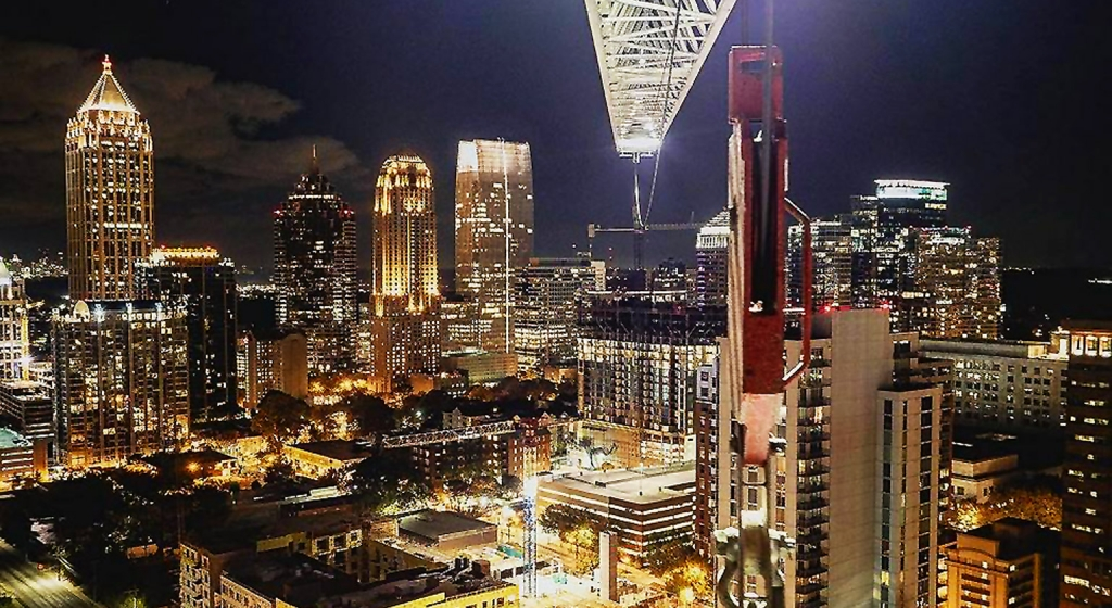 Skyline view of Atlanta at night with building crane overhead.